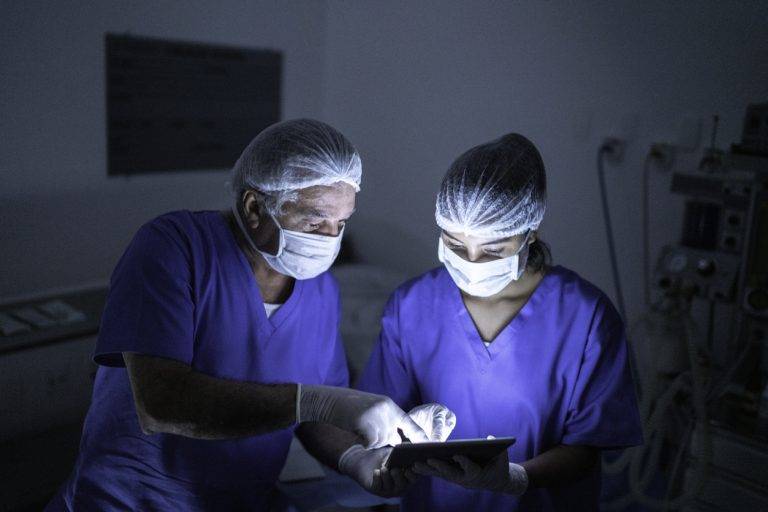 Two doctors at a hospital looking at medical images on a tablet